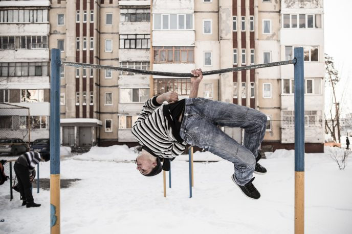 A young boy demonstrates acrobatic sports on a fixed bar in a playground of the Baykivskyi area of the city (built by architects from Azerbaidjan.