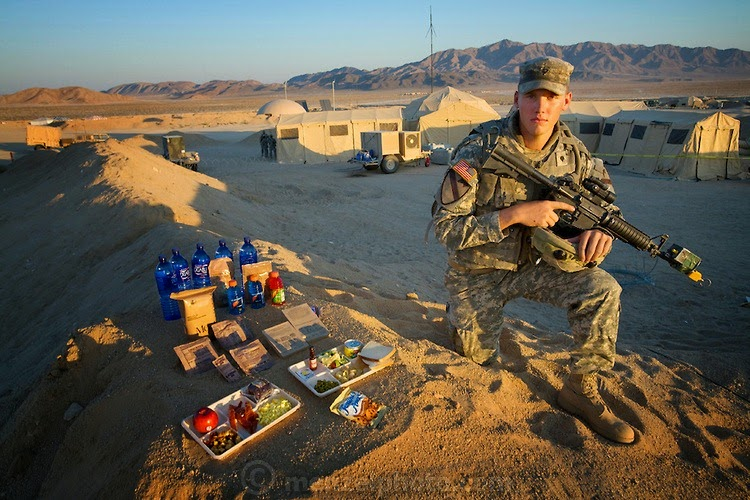"Curtis Newcomer, a U.S. Army soldier, with his typical day's worth of food at the National Training Center at Fort Irwin in California's Mojave Desert. (From the book What I Eat: Around the World in 80 Diets.) The caloric value of his day's worth of food in the month of September was 4,000 kcals. He is 20 years old; 6 feet, 5 inches tall; and 195 pounds. During a two-week stint before his second deployment to Iraq, he spends 12-hour shifts manning the radio communication tent (behind him). He eats his morning and evening meals in a mess hall tent, but his lunch consists of a variety of instant meals in the form of MREs (Meals, Ready-to-Eat). His least favorite is the cheese and veggie omelet. ""Everybody hates that one. It's horrible,"" he says. A mile behind him, toward the base of the mountains, is Medina Wasl, a fabricated Iraqi village—one of 13 built for training exercises, with hidden video cameras and microphones linked to the base control center for performance reviews. MODEL RELEASED."