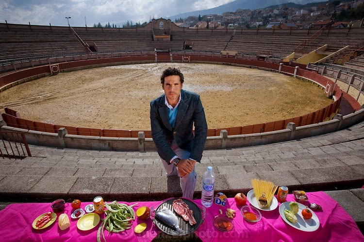 "Oscar Higares, a professional bullfighter, with his typical day's worth of food in the bullring in Miraflores De La Sierra, Spain, on a training day. (From the book What I Eat: Around the World in 80 Diets.) The caloric value of his typical day's worth of food in the month of April was 4,200 kcals. He is 34 years old; 6 feet, 2 inches tall; and 174 pounds. On the day of a bullfight, Oscar tries to sleep late and usually skips breakfast. Because he is a ""bit scared"" he isn't hungry and eats very little. ""The good months of bullfighting are August and September, and it's really hot. The jackets we have to wear are so tight, and they're really heavy. And the pressure of the people watching you—you have to be so concentrated. You lose weight. You lose two kilos [4.4 pounds] every time you go out."" He says that in the evening after a fight, ""dinner is big... I eat lots of meat."" MODEL RELEASED."