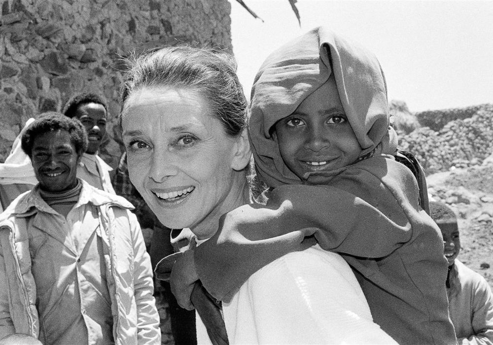 UNICEF Goodwill Ambassador Audrey Hepburn smiles as she carries a child on her back, in the northern town of Mehal Meda in Shoa Province. Ms. Hepburn was visiting a food distribution centre in the town. In 1988, internationally known film actor and UNICEF Goodwill Ambassador Audrey Hepburn travelled to Ethiopia on her first official UNICEF mission, to raise awareness of the impact of the continuing drought on the country's children and women. During her trip, sponsored by the United States Committee for UNICEF, Ms. Hepburn visited UNICEF-assisted health clinics and supplementary feeding programmes, 'food-for-work' projects, an income-generating project and an orphanage for children who have been abandoned or orphaned in this region during the drought. Ms. Hepburn was appointed a UNICEF Goodwill Ambassador on 9 March of this year.